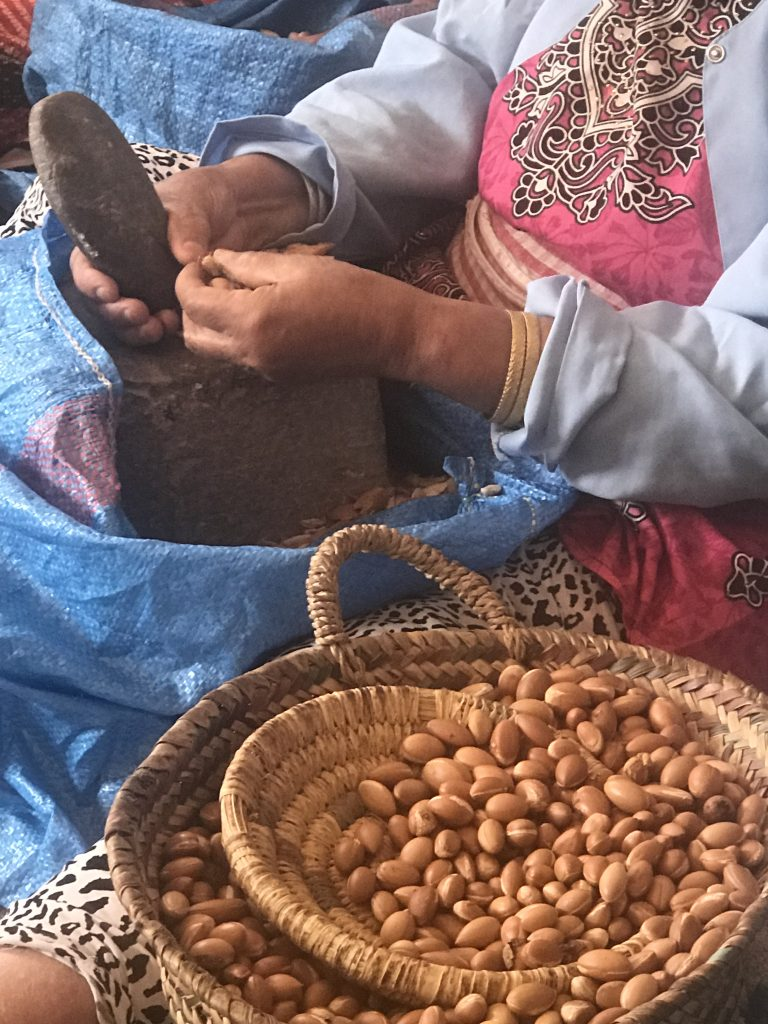 Woman cracking Argan nuts at Cooperative Tirizite Arazane Morocco - by Khadija Fajry