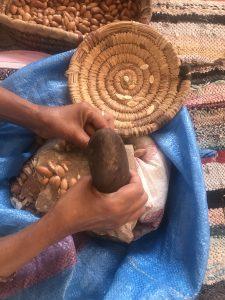 A Berber Woman Cracking Argan Nuts